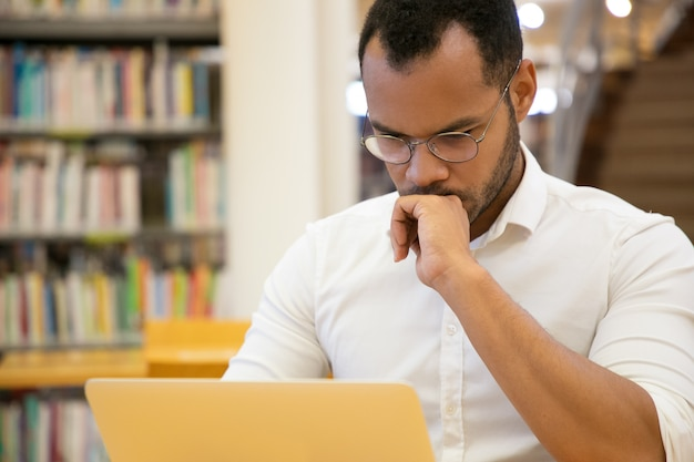 Focused young man holding hand on chin and looking at laptop Free Photo