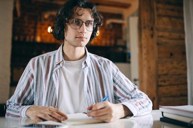 Сосредоточенный молодой человек в очках и беспроводных наушниках сидит за столом, слушая вебинар, образовательный курс, делая заметки. Бесплатные Фотографии