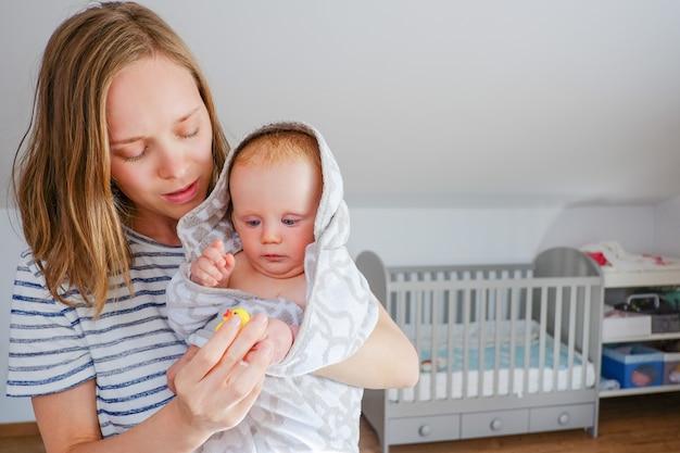 Сосредоточенная молодая мама держит сладкого сухого ребенка, завернутого в полотенце с капюшоном после душа, играет с резиновой игрушкой для купания. вид спереди, копия пространства. концепция ухода за детьми или купания Бесплатные Фотографии