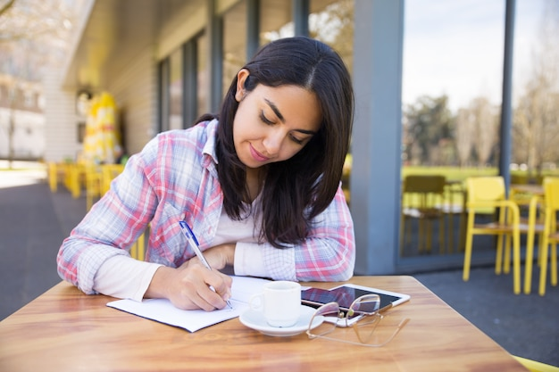 Focused young woman making notes in outdoor cafe Free Photo