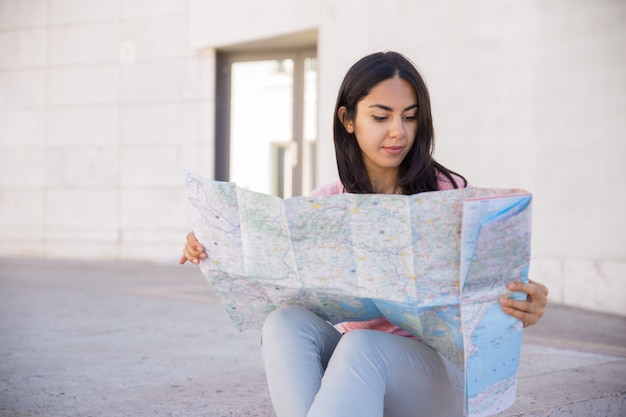 Focused young woman studying paper map outdoors Free Photo