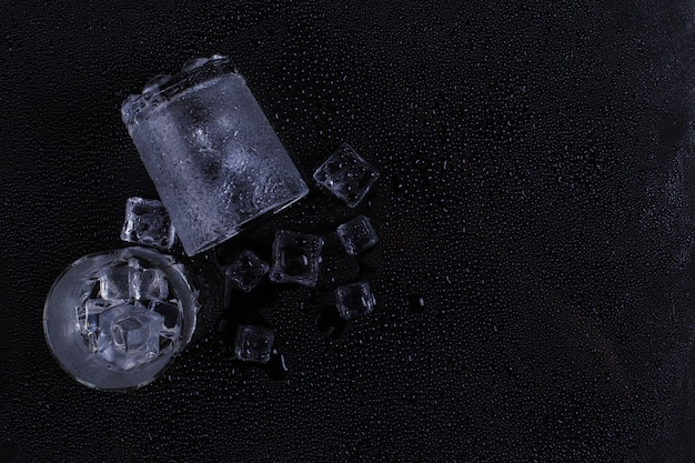 A foggy glass and ice lies on a black background Premium Photo