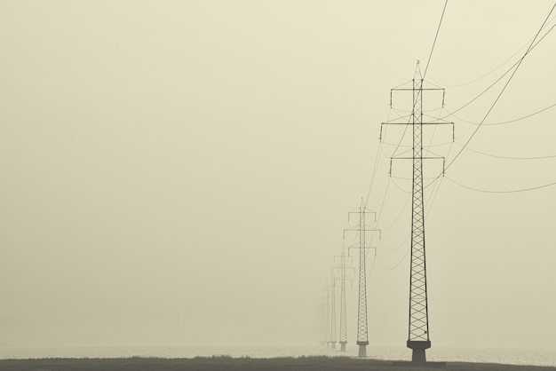Foggy shot of transmission towers in the middle of a street Free Photo
