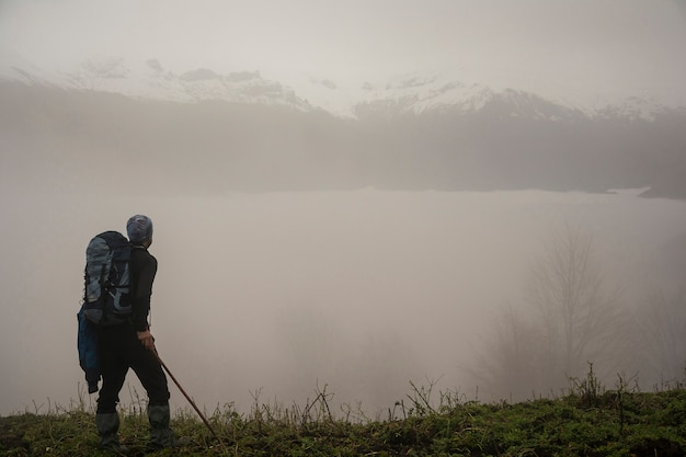 Fogy mountain hills and active hiker with backpack in foreground Premium Photo