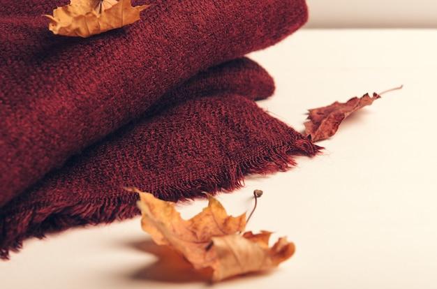 Folded burgundy scarf on white background with autumn leaves Premium Photo