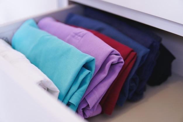 Сложенная разноцветная одежда разложена в шкафу под светом Бесплатные Фотографии