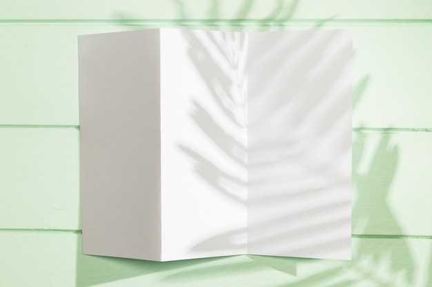 Folded paper with copy space and leaves shadow Free Photo