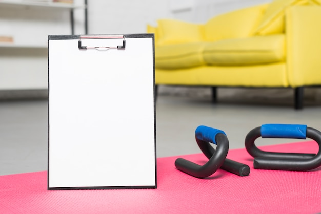 Folder on the floor next to fitness tools Free Photo