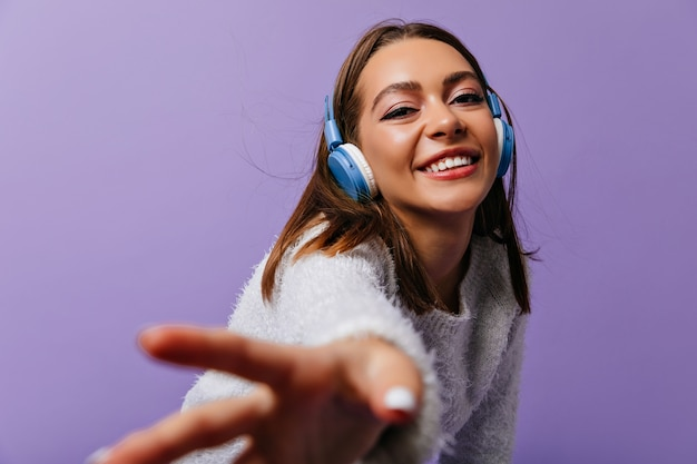 Follow me. attractive young woman of 24 years old calling to go with her. female student in headphones listens to positive song while posing for portrait Free Photo