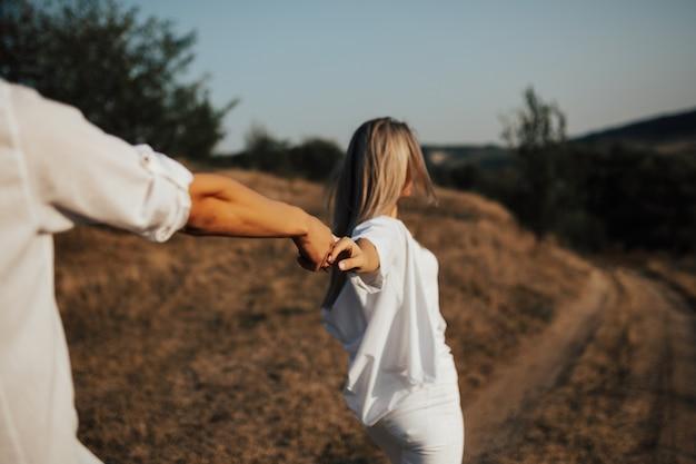 フォローしてください。手をつないで彼氏を散歩に導く白い服を着たかなり若い女性。 Premium写真