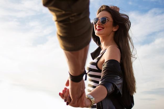 Подписывайтесь на меня. молодая красивая женщина тащит ее бойфренд, на открытом воздухе закат. Бесплатные Фотографии