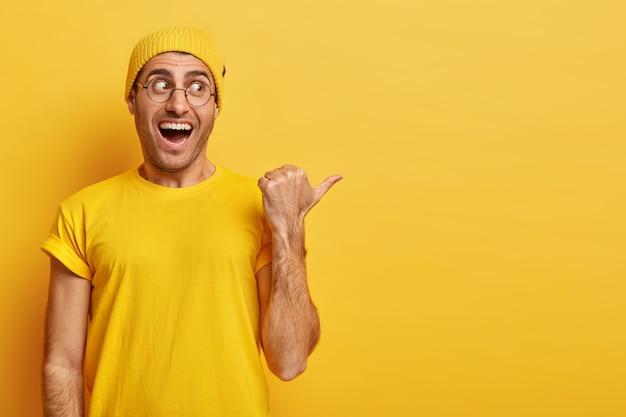 この方法に従ってください。大喜びの表情で幸せな若い男は、右側に親指を向ける 無料写真