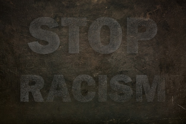 Font with transparency stop racism graffiti on a black stone background Premium Photo