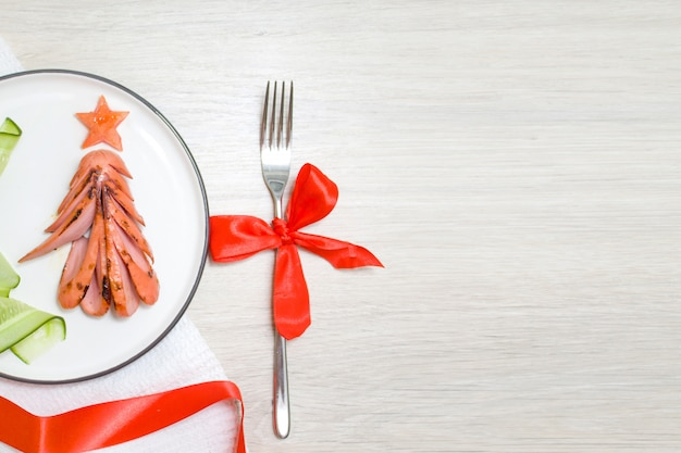 Food art concept. edible christmas tree made from fried grilled sausages, breakfast idea Premium Photo