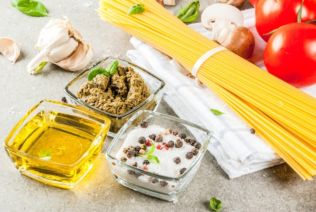 Food background ingredients for cooking dinner.  pasta spaghetti vegetables sauces and spices grey stone background Premium Photo