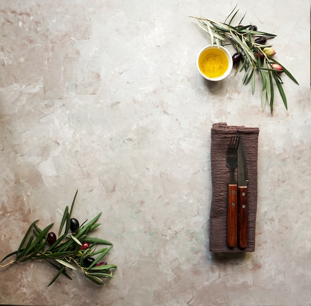 Food background with olive tree branch, napkin and plate, knife and fork cutlery, olive oil on concrete background Premium Photo