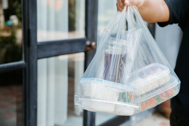 宅配業者が自宅に宅配したビニール袋入りフードボックス Premium写真