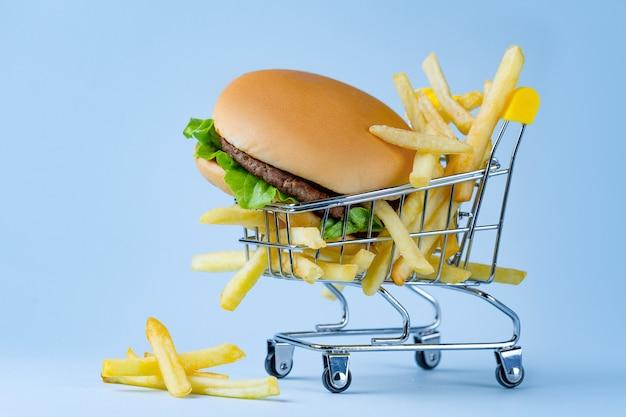 Концепция питания. картофель фри и гамбургер на закуску. нежелательная, углеводная и нездоровая пища. Premium Фотографии