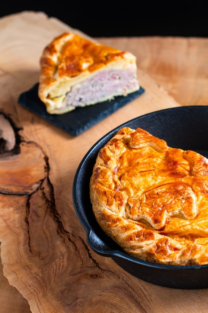 Food concept homemade pork pie or meat pie in cast iron skillet and stone plate on wooden background Premium Photo