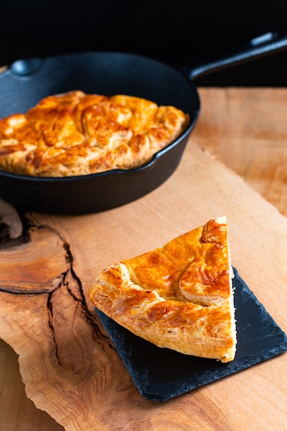 Food concept homemade pork pie or meat pie on stone plate and cast iron skillet on wooden background Premium Photo