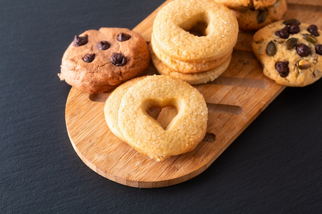 Food concept homemade sugar butter cookies on wooden board on black slate stone plate with copy space Premium Photo