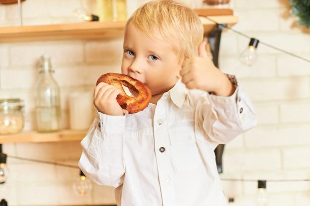 食品、料理、ペストリー、ベーカリーのコンセプト。キッチンで朝食時に焼きたてのベーグルを楽しんで、身振りで示す、親指を立てるサインを作るハンサムな青い目の小さな男の子の肖像画 無料写真