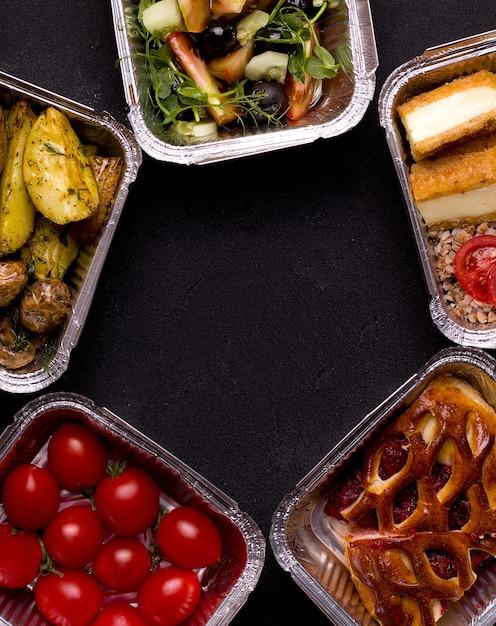 Концепция доставки еды. различные пищевые контейнеры на черном фоне. Premium Фотографии
