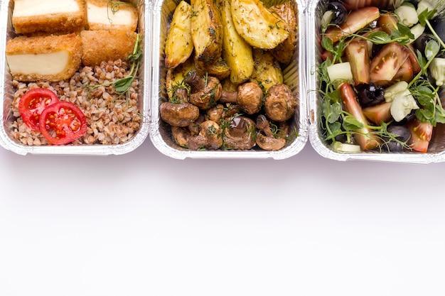 Концепция доставки еды. жареный картофель с грибами, салатом и гречкой в контейнере крупным планом. Premium Фотографии