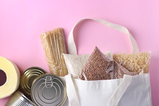 ピンクの表面に検疫隔離期間中の食料供給危機の食料ストックを備えた食料配達、寄付、繊維食料品バッグ。米、そば、パスタ、缶詰、トイレットペーパー、上面図 Premium写真