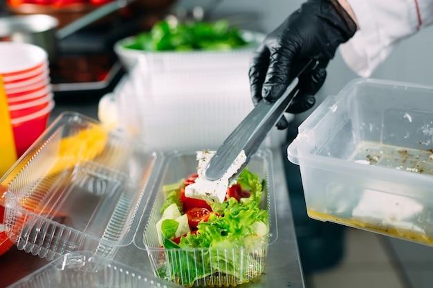 レストランでのフードデリバリー。シェフはレストランで料理を作り、使い捨ての料理に詰めます。 Premium写真