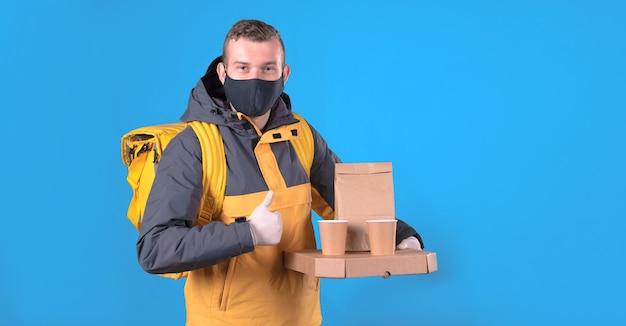 黄色いジャケットの医療マスクを持つ食品配達人 Premium写真