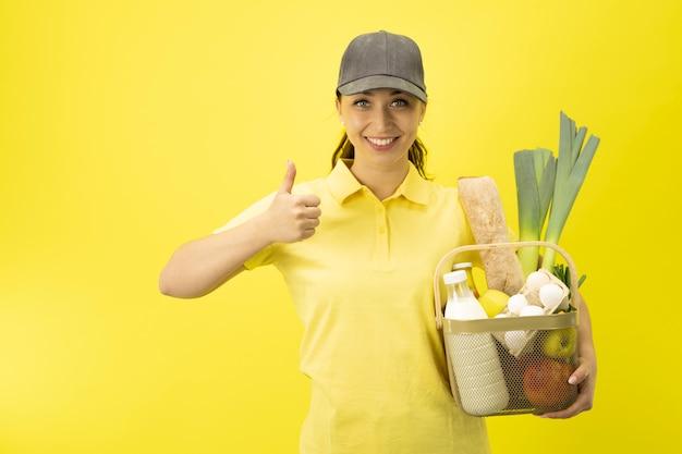 Девушка службы доставки еды с корзиной продуктов на желтой стене копией пространства Premium Фотографии