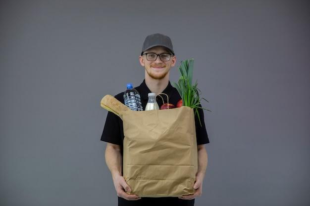 Человек службы доставки еды с коробкой продуктов на сером фоне с копией пространства Premium Фотографии