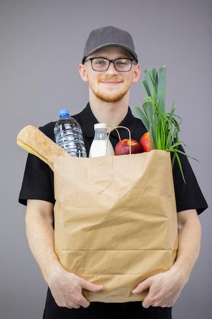 Человек службы доставки еды с коробкой бакалеи на серой изолированной стене Premium Фотографии