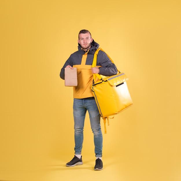 Доставка еды молодой человек в желтой куртке Premium Фотографии