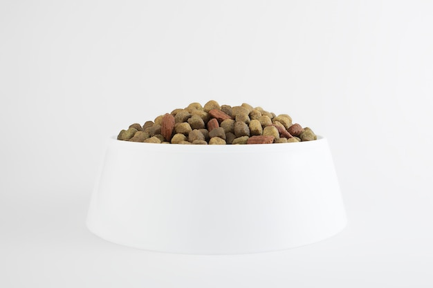 Food for a dog or cat. dry food for kittens or puppies close-up in a white bowl on a white Premium Photo