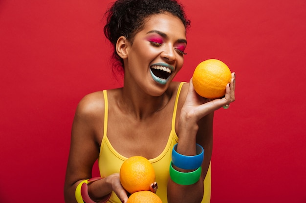 Food fashion joyful mixed-race woman with colorful makeup having fun holding lots of ripe oranges in hands, isolated over red wall Free Photo