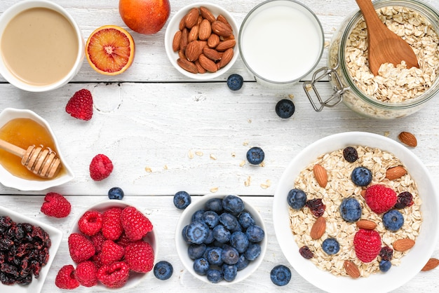 Food frame made of breakfast ingredient. muesli, fruits, berries, cappuccino, nony, milk and nuts. healthy food Premium Photo