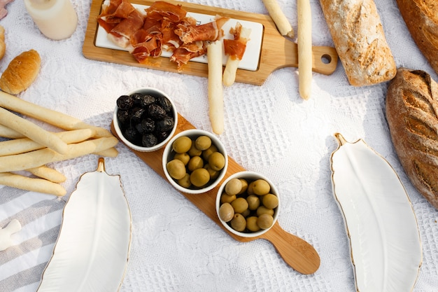 Food lay out on picnic blanket. fresh baked bread, olives and photocam lay on white blanket Premium Photo