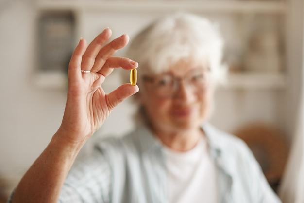食品、栄養、食事、健康の概念。魚油またはオメガ3多価不飽和脂肪酸サプリメントをカプセルの形で持っている年配の女性の手のクローズアップショット、昼食時に1つを取るつもり 無料写真