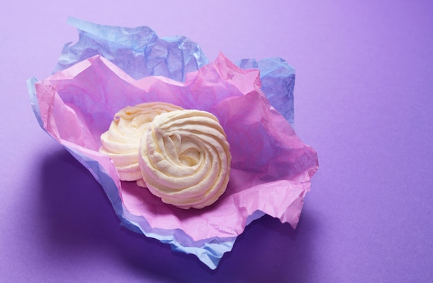 Food photo of homemade zephyr, marshmallow in violet wrapping paper. healthy sweet dessert on a pink background. Premium Photo