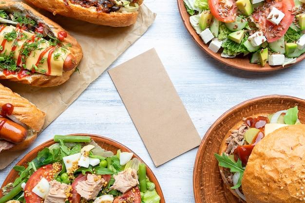 빈 공예 종이 음식 사진 벽입니다. 핫도그, 햄버거 및 샐러드로 구성. 길거리 음식 디자인을위한 훌륭한 이미지입니다. 공간 복사 프리미엄 사진