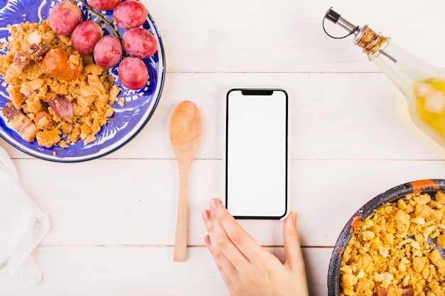 Food plates and hand with mobile phone on cooking table Free Photo
