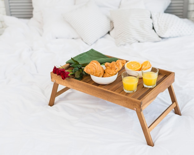 Food and roses on breakfast table on bed Free Photo
