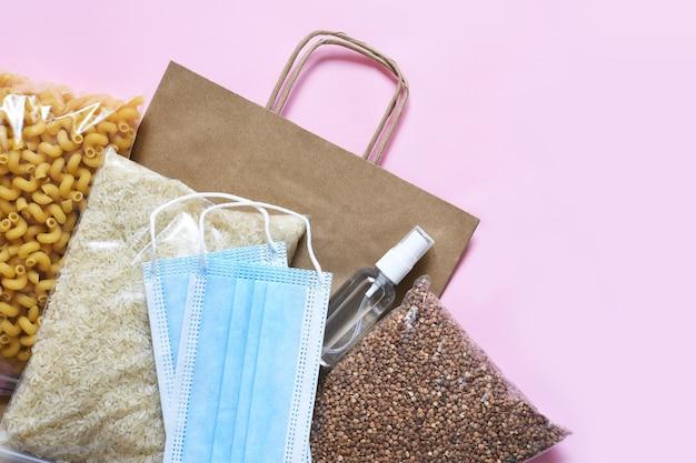 ピンクの背景に食料供給の危機。パスタ、そば、マスク、防腐剤、紙。寄付。平らに食べ物。 Premium写真