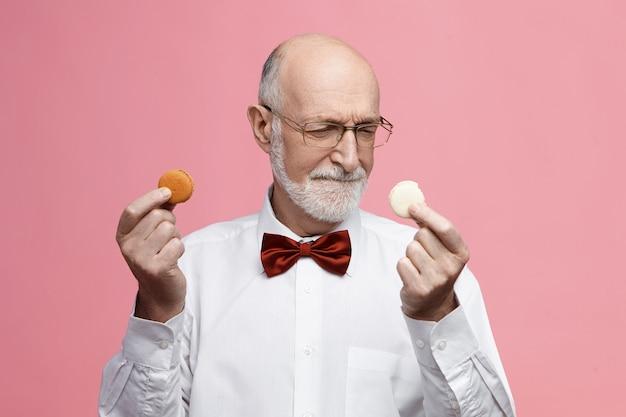 Concetto di cibo, dolci e prelibatezze. indeciso maschio barbuto senior avente un debole per i dolci che tiene due biscotti macarons colorati, accigliato, scegliendo tra loro, indossando occhiali e farfallino Foto Gratuite