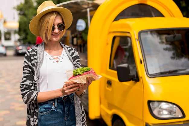 Food truck and woman holding a sandwich Free Photo