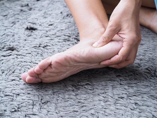 Травмы ног используйте ручной массаж ног, чтобы расслабить мышцы от болей в пятках Premium Фотографии