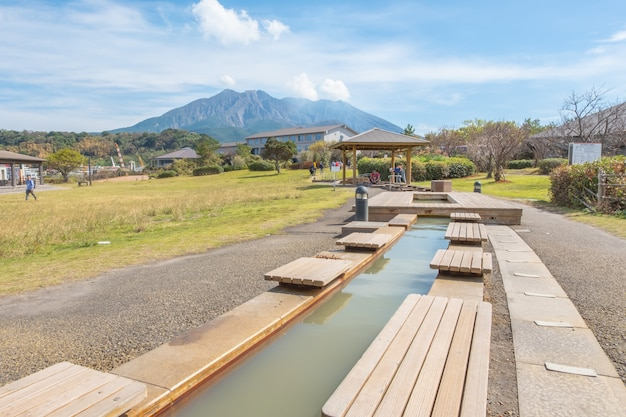 Foot onsen with sakurajima mountain, sea and blue sky background,  kagoshima, kyushu, japan Premium Photo