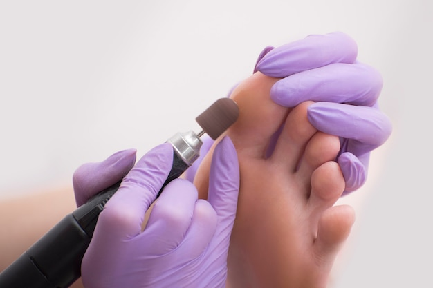 Foot skin treatment process. gloved hands with a pedicure machine. close-up Premium Photo